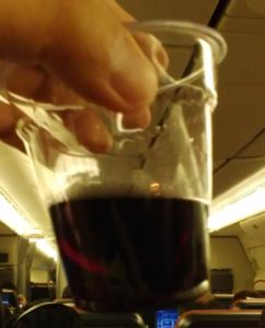 """飛行機内で撮影したプラスチックコップに入った「DOUBLE""""O""""」赤ワイン"""